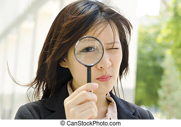 Quality control - Asian business woman with magnifying glass...