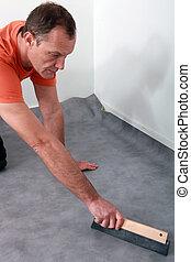 Man laying carpet at home
