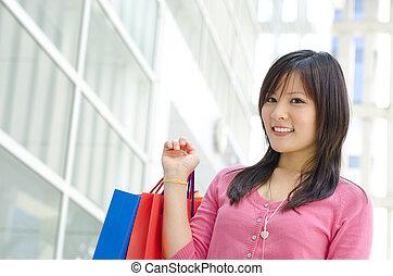Beautiful shopper - Beautiful young Asian girl holding paper...