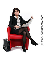 Businesswoman reading the newspaper