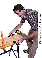 Carpenter measuring wood on a workbench