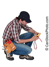 A kneeling electrician with a voltmeter.