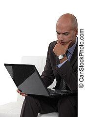 Pensive bald man using laptop