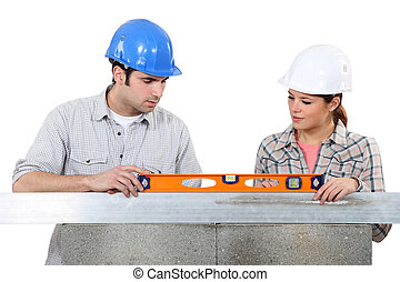 Couple using spirit-level on wall