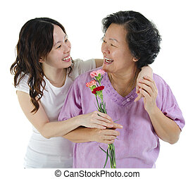 Thank you mother - Young Asian girl carnation flower to her...