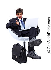 Boy dressed in a businessman using a laptop computer making a 'telephone' sign with his hand