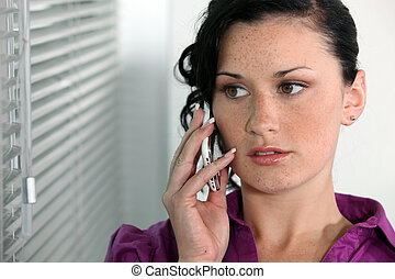 Attractive young woman talking on her mobile phone