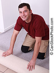 Horizontal image of a man laying carpet