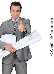 Man dressed in suite holding hard hat and blue-prints