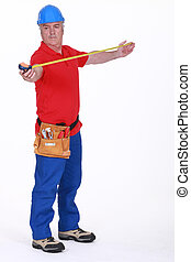 Grey-haired handyman using tape measure