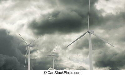 Wind Generators and Clouds - Wind turbines spinning with a...