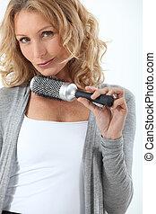 Hair-dresser holding hair-brush