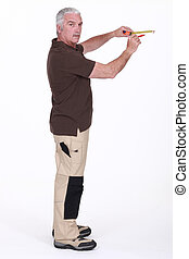 Grey-haired man measuring wall