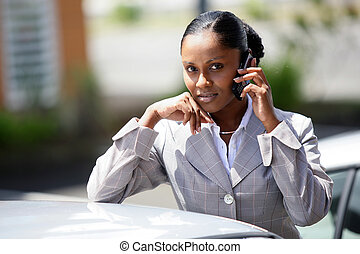 Businesswoman making a call by her car