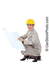 Female architect kneeling with blueprints