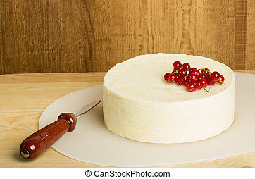 White cheddar cheese with knife and currants
