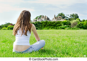Woman sitting on green lawn on park