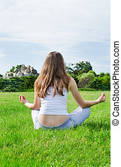 Woman meditates on green lawn on the park