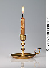Lighted candle in an old brass candlestick, with a gray...