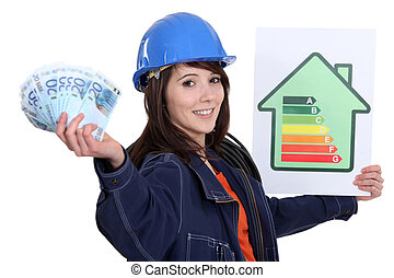 Tradeswoman holding up an energy efficiency rating chart and...