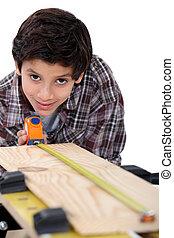 Boy carpenter measuring wood