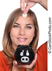 Woman holding piggy bank and coin