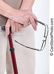 Closeup detail of senior's glasses and walking stick