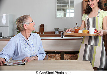 Elderly lady being brought breakfast