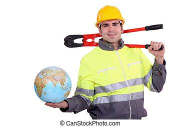 Smiling laborer holding a globe, studio shot