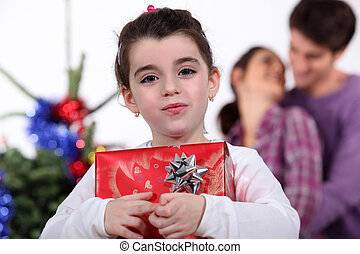 Young girl holding a gift on Christmas Day