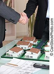 Handshake over a model housing estate