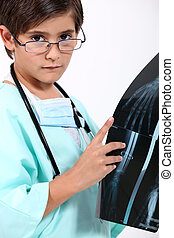 little boy dressed as a doctor looking at a x-ray image