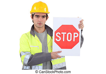 Worker holding stop sign