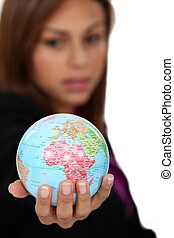 Businesswoman holding globe