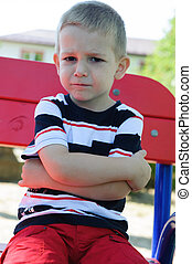 Serious little boy sitting at playground - Serious little...