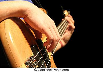 Bass Guitar - A bass guitar player plucks the strings