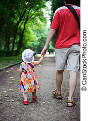 Young father and his little daughter walking in the park