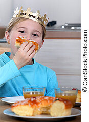 Little girl eating cake whilst wearing a crown
