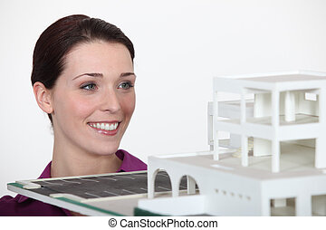 A female architect showing her model.
