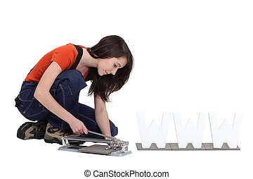 Woman using a manual tile cutter