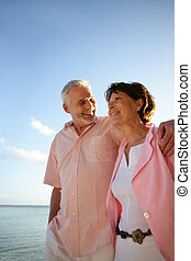 Middle-aged couple taking a stroll by the beach