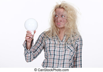 Shocked blond woman holding light bulb