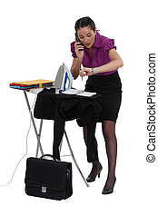 Late businesswoman ironing a suit jacket
