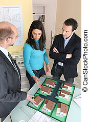 Couple looking at plans with an architect