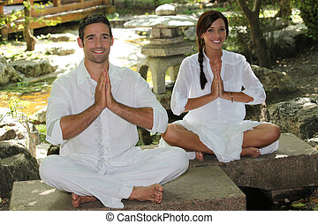 Man and woman sat in garden meditating