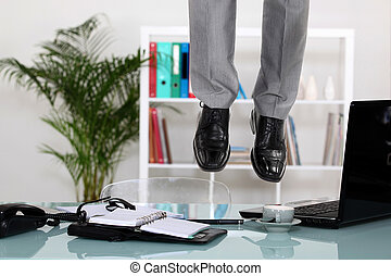 Businessman hanging from ceiling