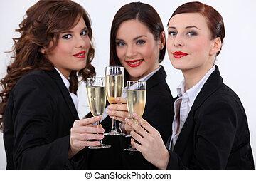 Three businesswomen drinking champagne