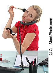 Woman putting her makeup on in the office