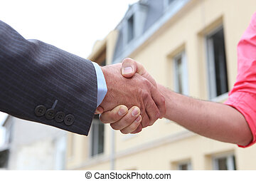 Couple shaking hands outside a house