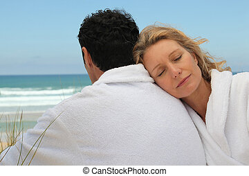 Husband and wife on the beach in bath robes